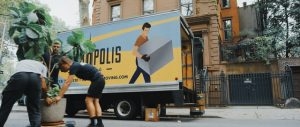 People carrying a plant in front of a yellow and blue moving truck